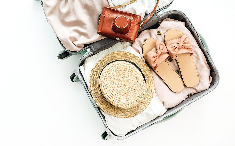 A imagem mostra uma mala sendo preparada para uma viagem com um sapato, chapéu, roupas e máquina fotográfica. Simbolizando tudo que é essencial para uma viagem.