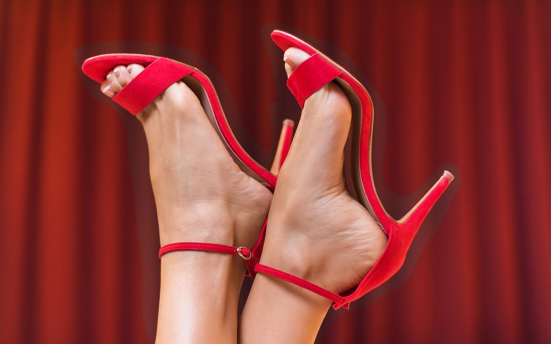Mulher de pernas para o ar com uma sandália clássica de tiras na cor vermelho